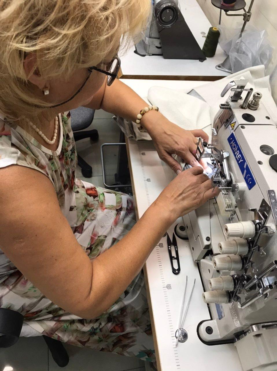 Opératrice assemblant les manches du Sweatshirt Capuche Brasseur